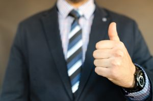 A man with thumbs up - like you might get when getting approved.