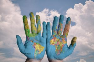 Hands with the world map painted on them.