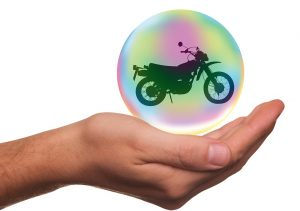 a motorcycle in a little bubble over hand as a reminder don't forget to insure stored property