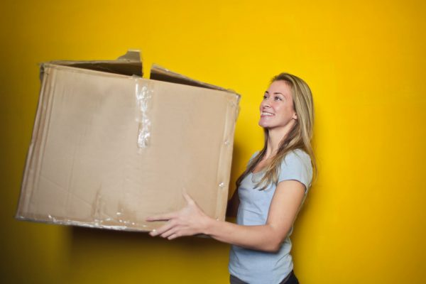 A woman holding a moving box to be used when packing collectibles for international transport.