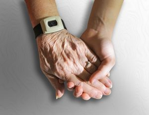 Hands of older person in young person's hand