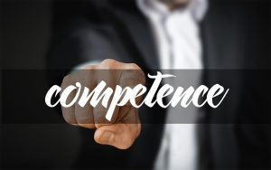 A man in a business suit pointing to the word competence.
