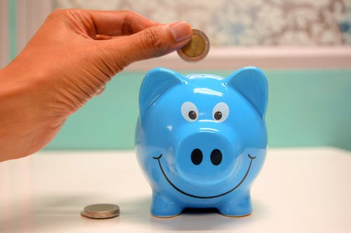 tips on how to save money while moving with a blue piggy bank