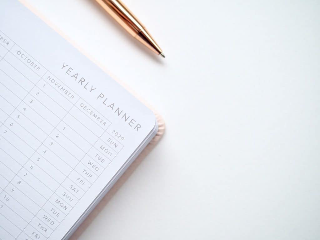 A yearly planner and a gold pen. Here's how to choose the best time of the year to move.