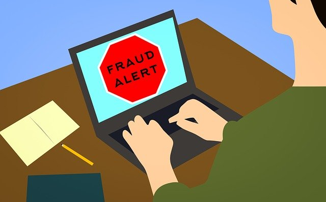 Illustration of a man using laptop with fraud alert sign on it
