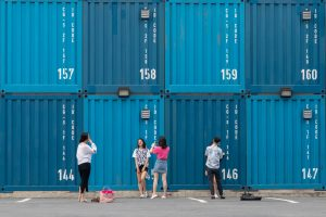 five women and man standing near shipping containers