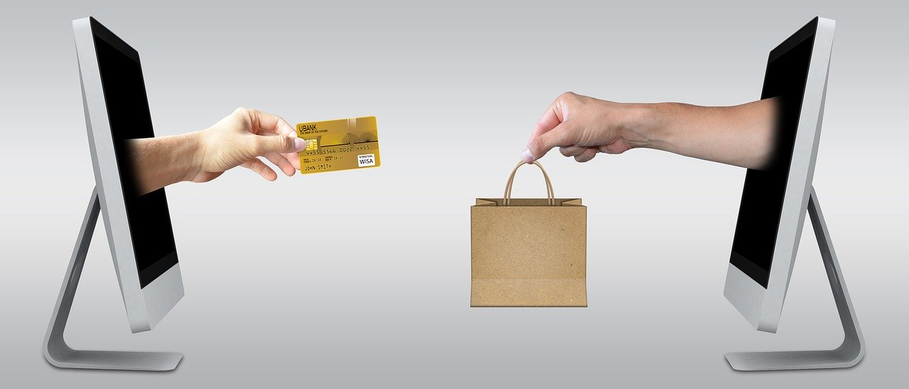 Two computers exchange goods for credit card which shows how e-commerce packing tips could be useful for many purposes