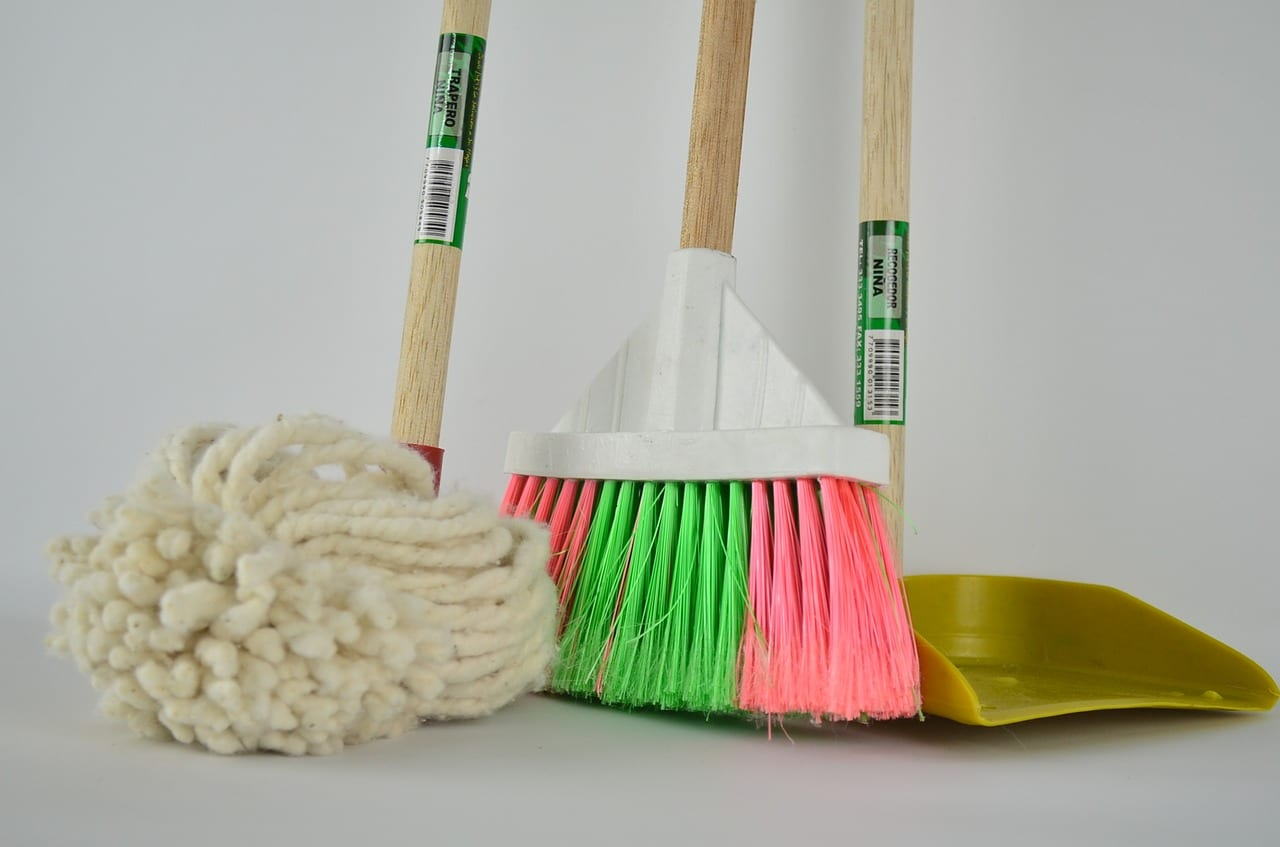 a broom, a mop and a duster next to eachother