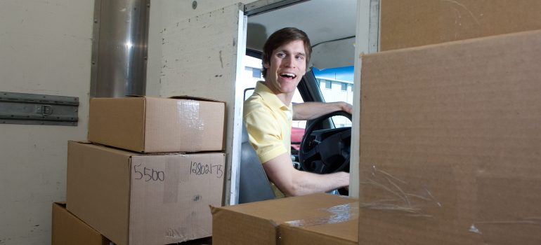 a delivery man smiling in the delivery truck