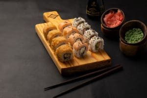 Sushi rolls on brown wooden tray