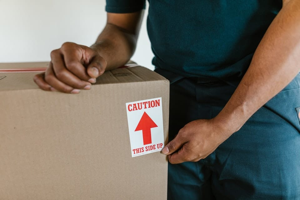 Aman holding a shipping box with a label