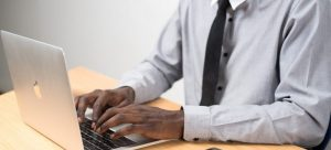 A person typing on the keyboard of the laptop
