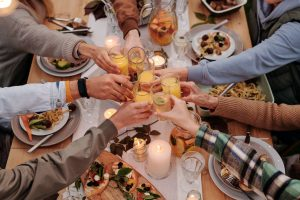 Throwing a housewaming party will make you want to unpack faster, so toast with your friends and family over dinner like the people in the photo
