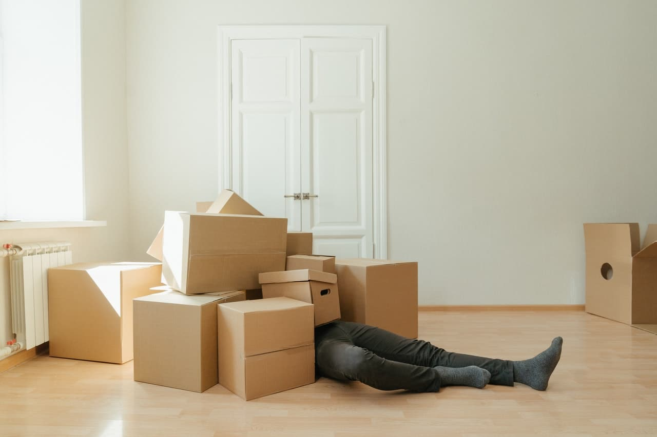 There are plenty of ways to beat unpacking procrastination after moving, get to work and clear out those boxes so you don't end up covered in them like the man in the picture.