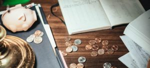 Coins and papers scattered on a wooden desk next to a piggy wallet