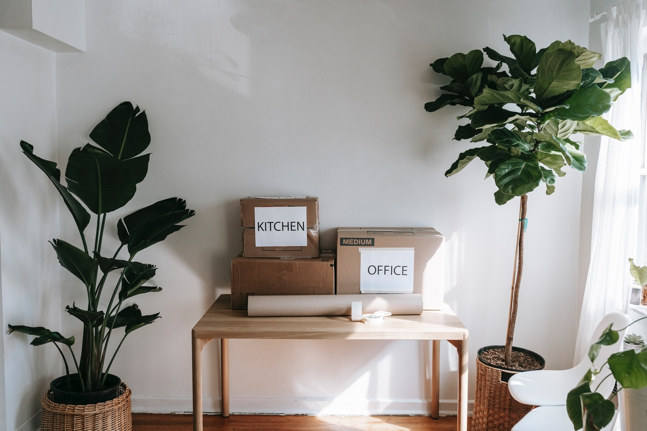 Boxes labeled as kitchen and office on a table